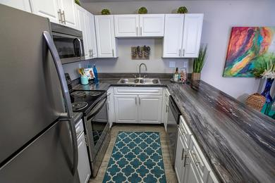 Updated Kitchens | Large kitchens featuring above range microwaves, granite-style counter tops, and an ample amount of cabinets.