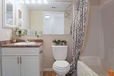 Remodeled Bathrooms | Beautiful remodeled bathrooms featuring wood-style flooring, granite-style counter tops, and large mirrors.