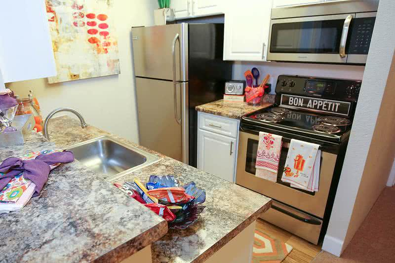 Updated Kitchen | Newly remodeled kitchen with white cabinetry and granite-style counter tops.