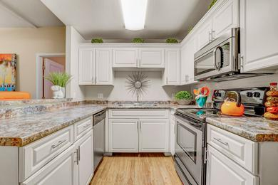 Designer Kitchen | Newly renovated kitchens featuring a large breakfast bar, granite-style counter tops, and ample cabinetry.