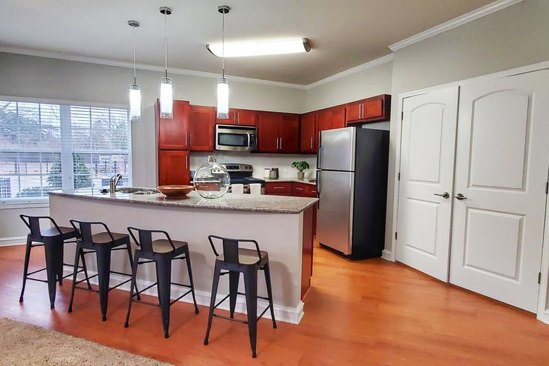 Open Kitchens with Granite Countertops | Our gorgeous open kitchens with cherry wood cabinetry and granite countertops are equipped with stainless steel appliances; microwave, stove, refrigerator and dishwasher.