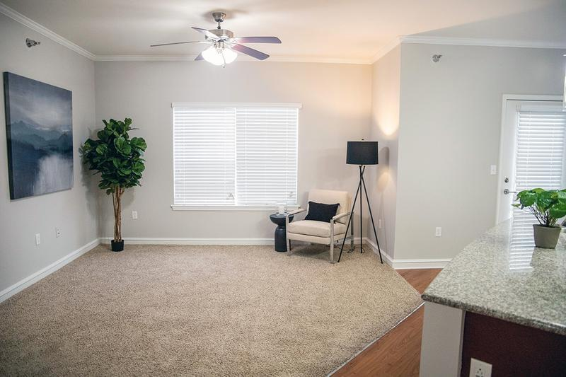 Spacious Living Room | Spacious open living rooms featuring multi-speed ceiling fans, plush carpeting and large windows.