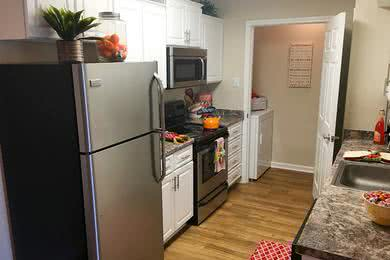 Kitchen | Newly remodeled kitchens featuring updated countertops and cabinetry, wood-style flooring, and washer and a laundry room.