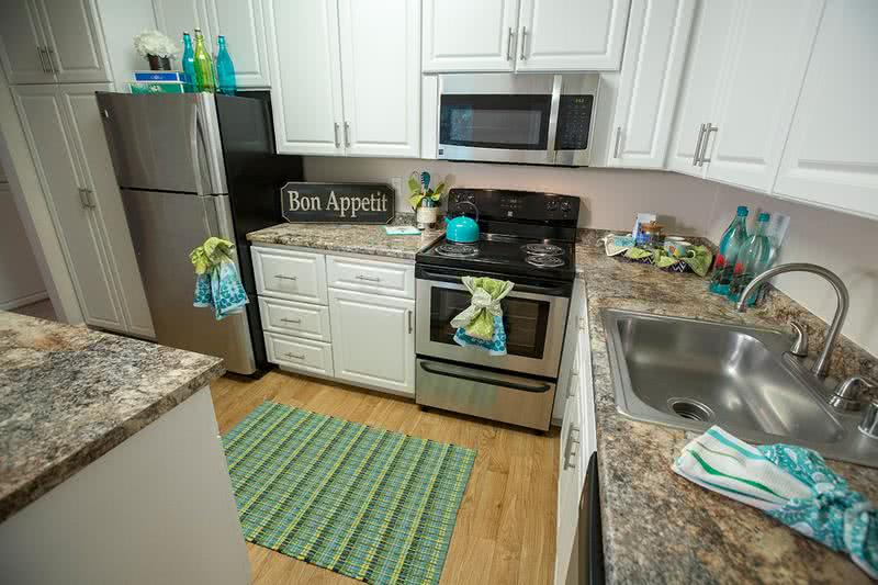 Kitchen | Newly remodeled kitchen with updated cabinetry featuring brush-nickle hardware, granite-style counter tops all electric appliances. (stainless steel in select apartments)