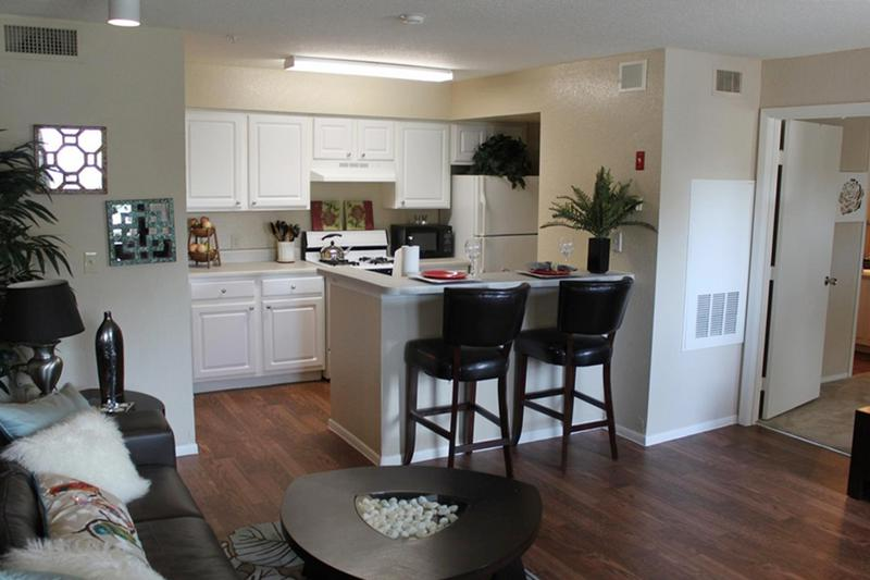 Kitchen | Fully applianced kitchens featuring wood-style flooring, ample cabinetry, and a breakfast bar.