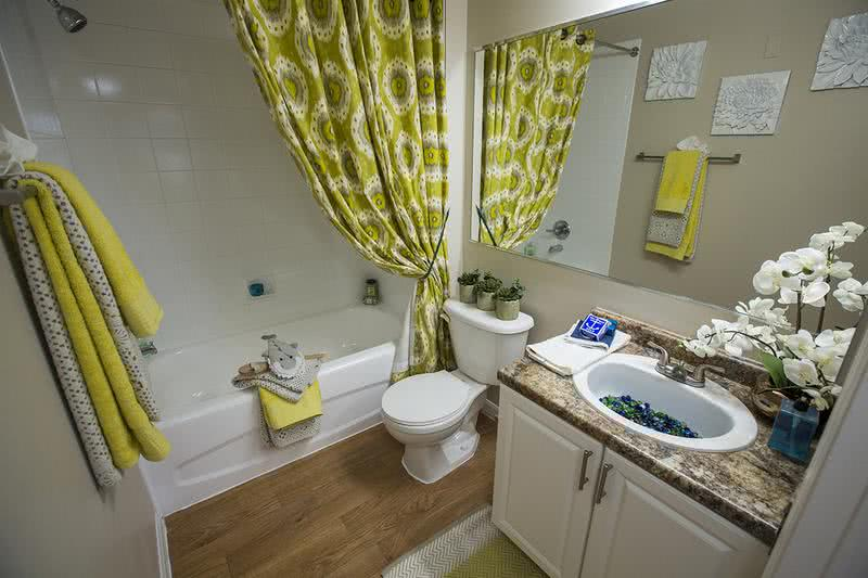 Bathroom | Bathrooms feature large mirrors, wood-style flooring, and granite-style counter tops.