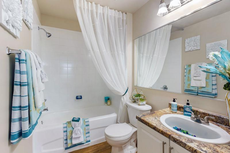 Guest Bathroom | Bathrooms feature large mirrors, wood-style flooring, and granite-style counter tops.