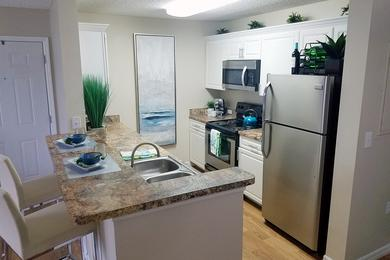 Updated Kitchens | Newly renovated kitchens featuring wood-style flooring, granite-style counter tops, and stainless steel appliances.