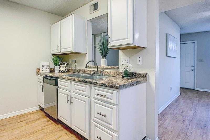 Updated Kitchens | Updated kitchens also feature white cabinetry and wood-style flooring.