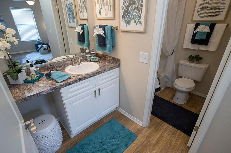Bathroom | Updated bathrooms featuring large mirrors and new countertops and cabinetry coming soon!