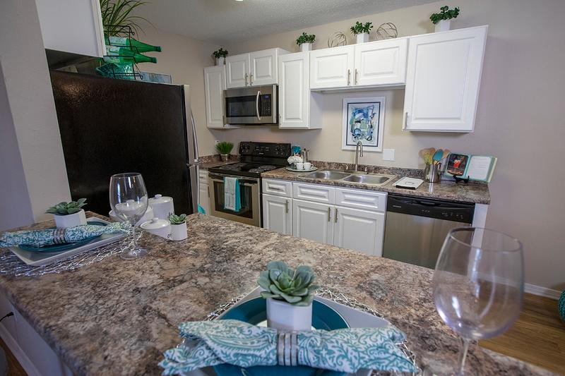 Updated Kitchens | Newly remodeled kitchens featuring white cabinetry, granite-style counter tops, wood-style flooring, and stainless steel appliances.