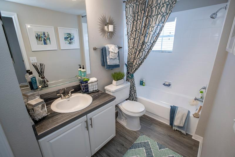 Bathroom | Updated bathrooms with updated counter tops, wood-style flooring, and large mirrors.
