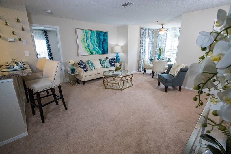 Living Room | Spacious living rooms with plush carpeting and a solarium, which is a perfect place for a small dining room table.