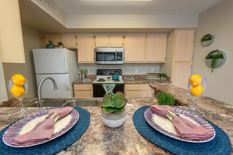 Kitchens | Spacious kitchens featuring granite-style countertops and wood-style flooring.