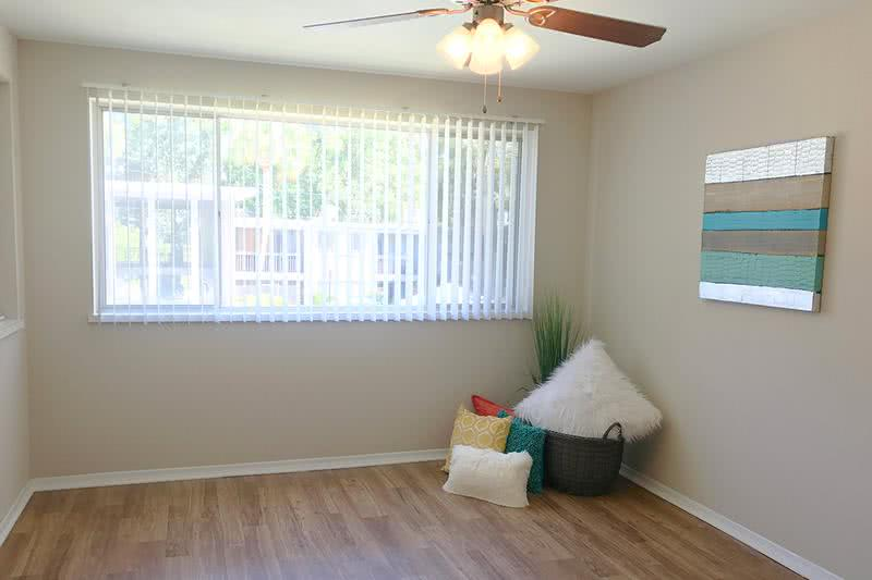 Bedroom | Spacious bedrooms featuring wood-style flooring, large windows, and a ceiling fan.