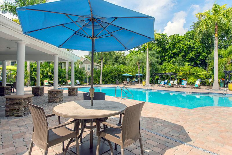 Poolside Tables | Enjoy sitting under one of our poolside tables with umbrellas.