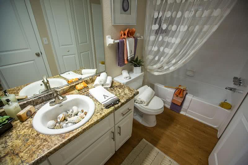 Bathroom | Designer bathroom with new granite style counter tops and modern vanity with exceptional storage space.