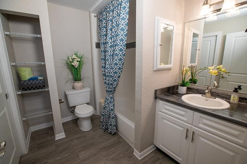 Updated Bathrooms | Newly renovated bathrooms featuring large mirrors, black fusion counter tops, and wood-style flooring.