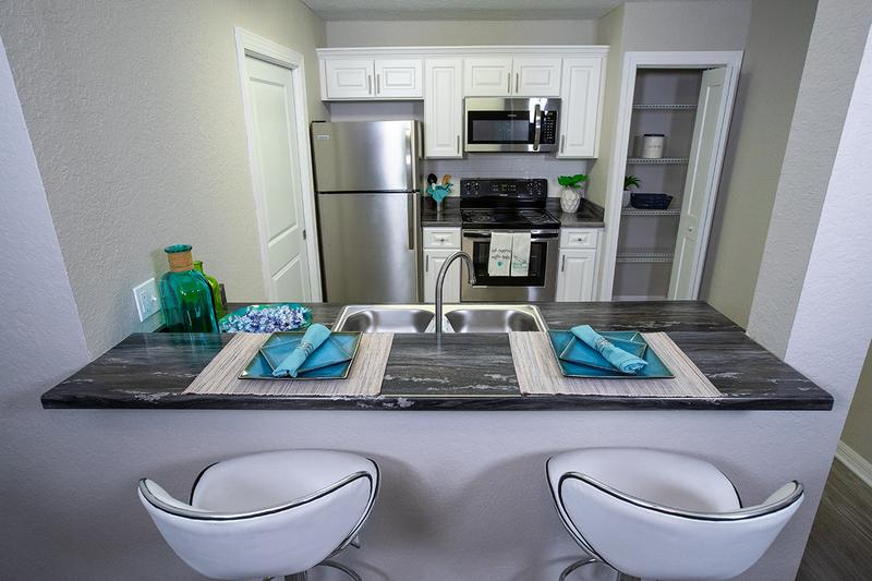 Newly Remodeled Kitchens | Your newly renovated kitchen features black-fusion countertops, wood-style flooring, and stainless steel appliances.