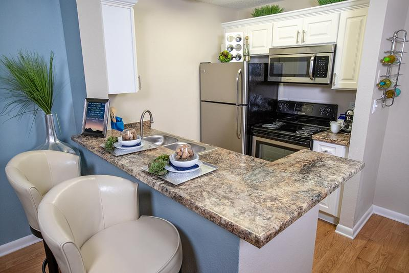 Kitchen | Newly updated kitchens with white cabinetry, granite counter tops, and stainless steel appliances.