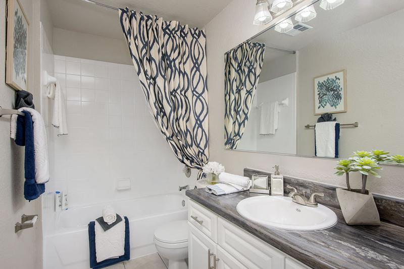 Updated Bathrooms | Newly remodeled bathrooms featuring black fusion counter tops, wood-style flooring, and large mirrors.