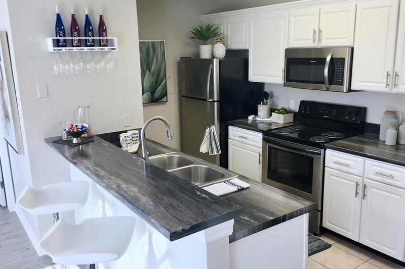 Renovated Kitchens | Newly renovated kitchens with black fusion countertops, wood-style flooring and a breakfast bar.
