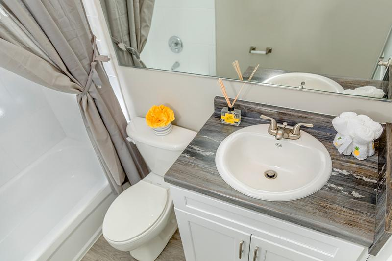 Renovated Bathrooms | Newly renovated bathrooms featuring black fusion countertops, large mirrors, and wood-style flooring.
