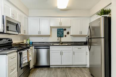 Renovated Kitchens | Newly renovated kitchens with black fusion countertops, wood-style flooring and a breakfast bar. Your kitchen also features full size washer and dryer appliances for your convenience.