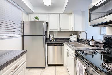 Kitchen | Newly renovated kitchens featuring black fusion countertops and ample cabinetry.