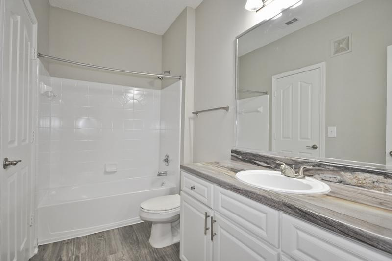 Bathroom | Updated bathrooms with black fusion counter tops, wood-style flooring, and large mirrors.