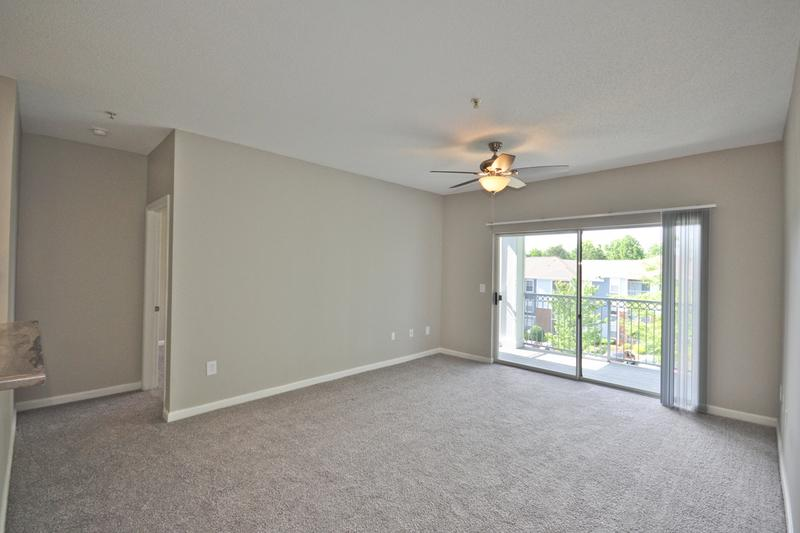 Living Room | Spacious living rooms featuring plush carpeting and sliding doors to your very own private patio.