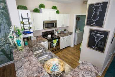 Breakfast Bar | Newly updated kitchens with granite-style counter tops, white cabinetry and wood-style flooring.