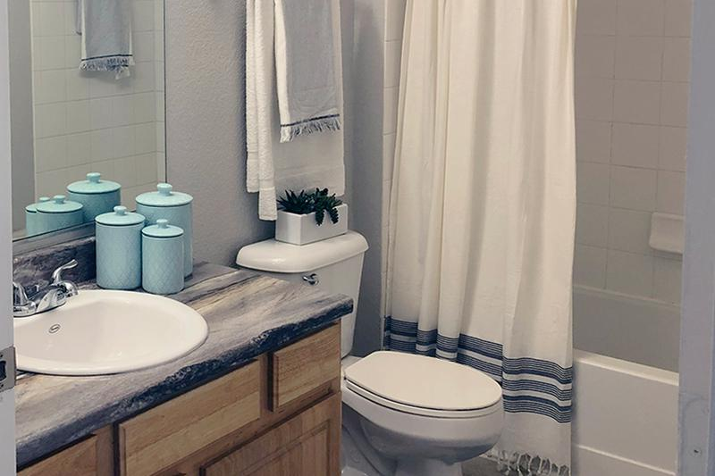 Modern Bathroom | Our renovated apartment homes feature black fusion coutnertops, and wood-style flooring.