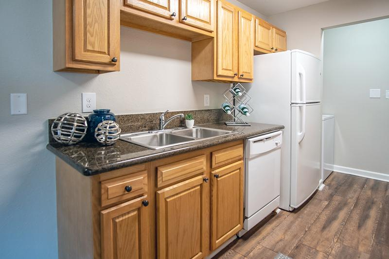 Updated Kitchens in Select Units | Newly renovated kitchens featuring black fusion countertops and wood style flooring.