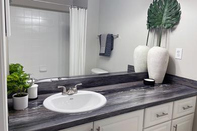 Bathroom | Bathrooms featuring black fusion counter tops, tile flooring, and large mirrors.