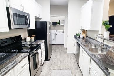 Fully Renovated Kitchens | Our renovated kitchens feature wood-style flooring, white cabinetry, and stainless steel appliances.