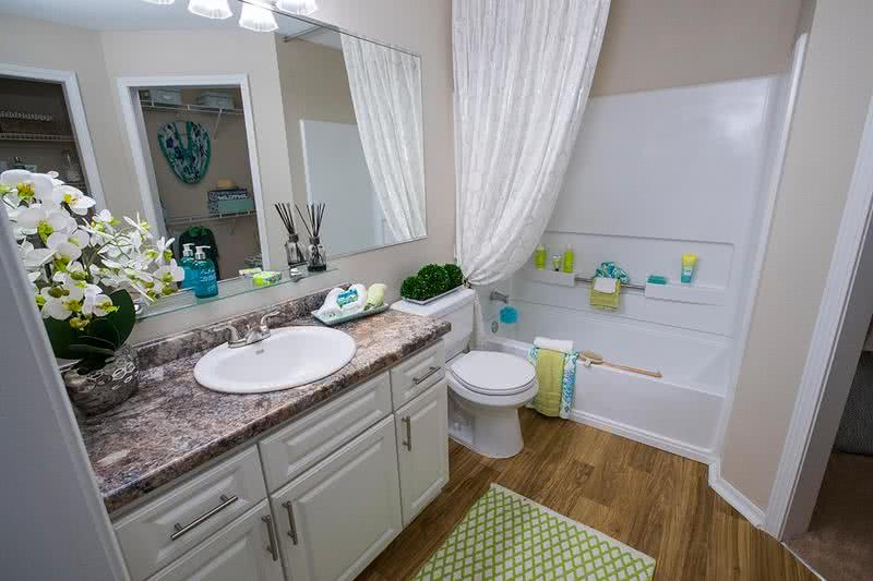 Bathroom | Newly renovated bathrooms with granite-style counter tops and wood-style flooring.
