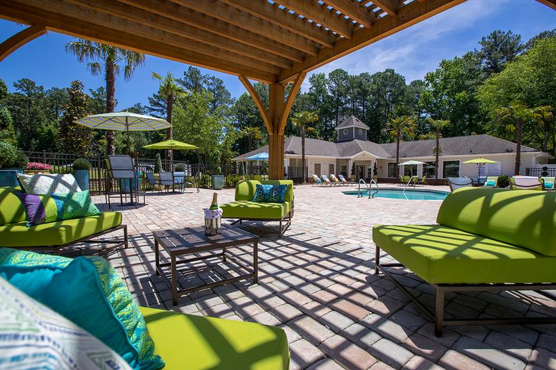 Poolside Pergola | Relax in the shade under the poolside pergola featuring comfortable seating.