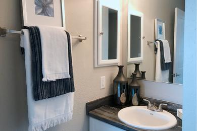 Bathroom | Updated bathrooms with black-fusion counter tops, large mirrors, and wood-style flooring.