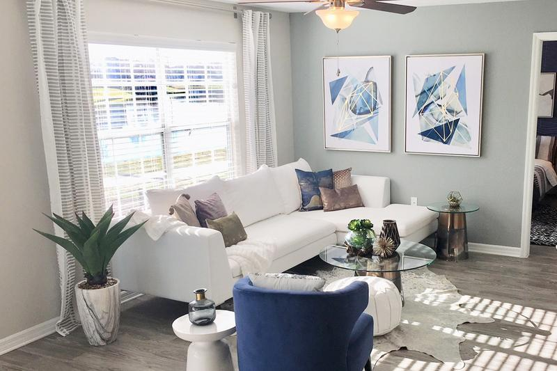Spacious Living Rooms | We are excited to offer in-person tours while following social distancing and we encourage all visitors to wear a face covering. Spacious living rooms with wood-style flooring and a ceiling fan.