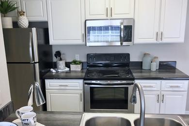 Stainless Steel Appliances | Updated kitchens featuring stainless steel appliances, black-fusion counter tops and white cabinetry.