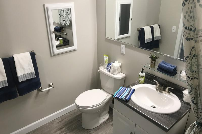 4x4 Bathroom | Each private bathroom offers large vanities and built-in medicine cabinets with a sleek, modern finish.