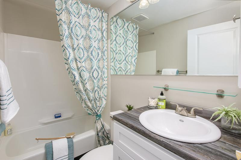 Remodeled 1 Bedroom Bathroom | Our newly remodeled bathrooms feature black fusion countertops, wood-style flooring, and large mirror.