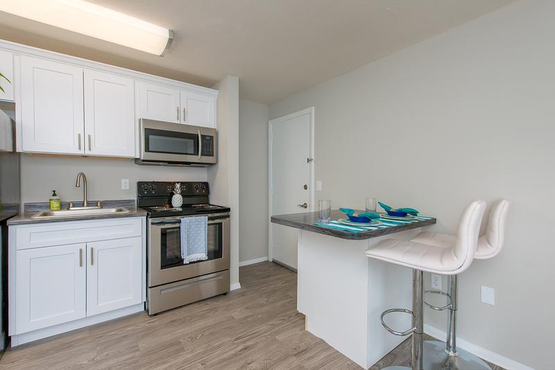 Remodeled 1 Bedroom Kitchen | Our newly remodeled apartments feature black fusion countertops, stainless steel appliances, and wood-style flooring.