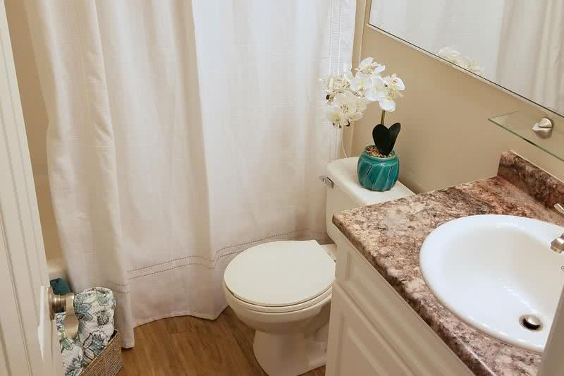 Updated Bathroom | Newly renovated bathrooms featuring granite-style countertops, large mirrors, and wood-style flooring.