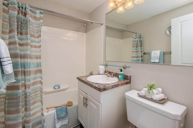 Bathroom | Updated bathrooms featuring granite-style counters and large mirrors.