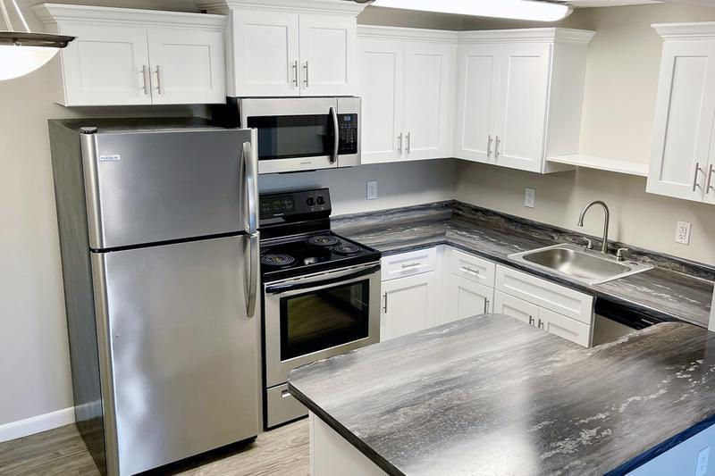 Black Fusion Kitchen | Updated kitchens with black fusion countertops, wood-style flooring, and stainless steel appliances. We are excited to offer in-person tours while following social distancing and we encourage all visitors to wear a face covering.