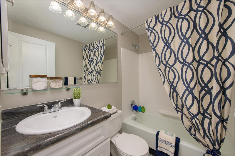 Bathroom | Newly remodeled bathrooms featuring wood-style flooring and black fusion counter tops.