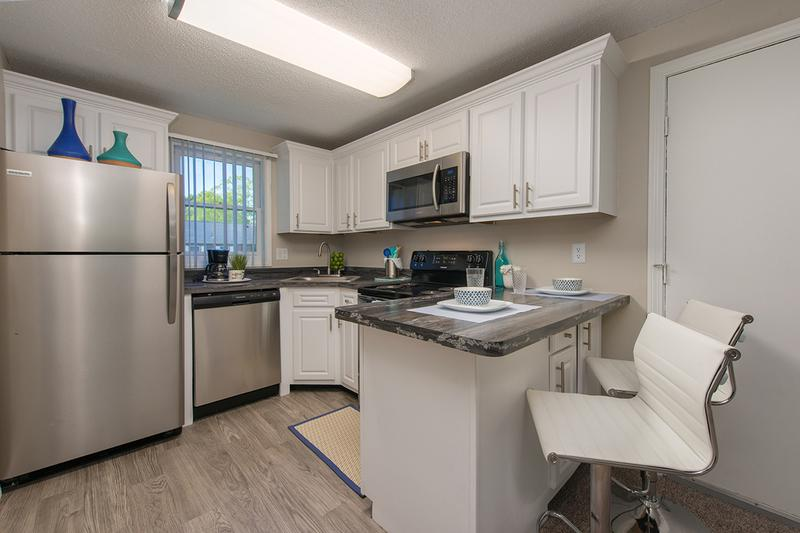 Updated Kitchens | Newly renovated kitchens featuring black fusion counter tops, wood-style flooring, and stainless steel appliances. We are excited to offer in-person tours while following social distancing and we encourage all visitors to wear a face covering.