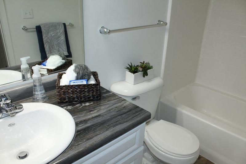 Renovated Bathrooms - In Select Homes | Updated bathrooms featuring black fusion countertops, wood-style flooring, and large mirrors.